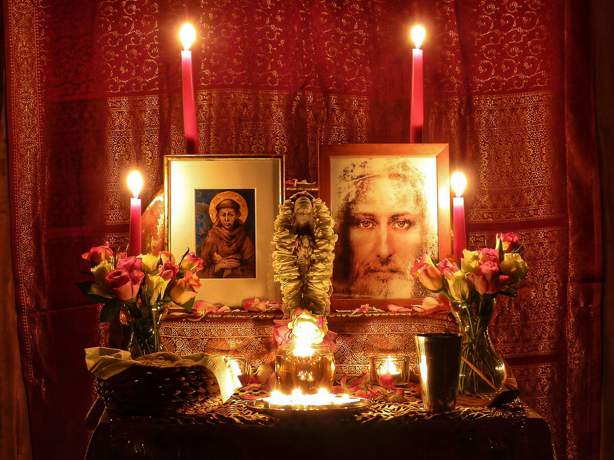 A Christian shrine featuring images of Christ and St Francis with candles